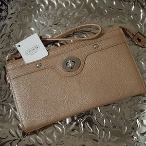 Coach leather zippy wallet with wrist strap.